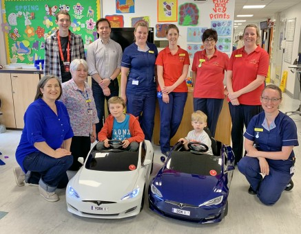 Children's Ward team with Alex and Luca Tesla Car